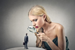 beautiful woman looking little man with magnifying glass